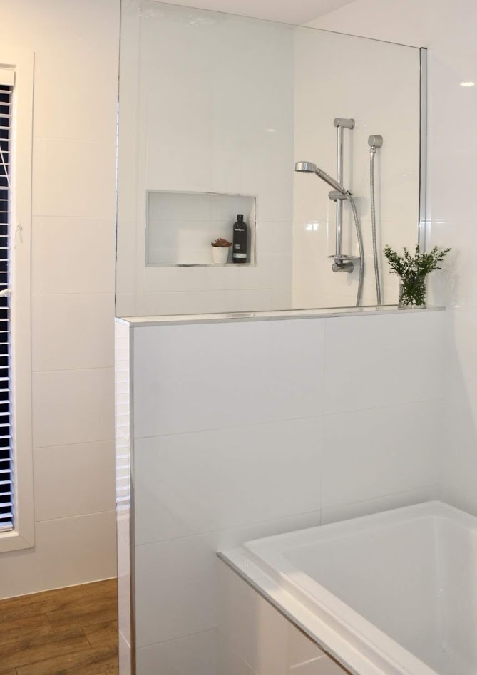 There is nothing like a window in your shower.  Timber look tiles look great in this bathroom.  A shower wall niche is great for storage.