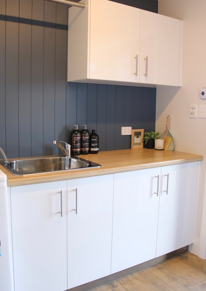 VJ panelling by easycraft makes this a cute laundry with Natural Oak laminate benchtops. Laundry hanging rail with timber tiles.