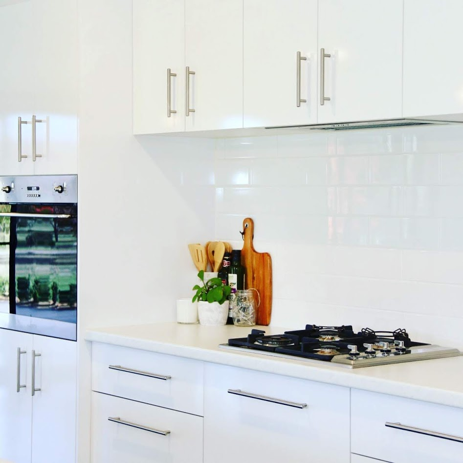 Classic white kitchen with subway splashback tiles.  A Smeg wall oven and gas cooktop.