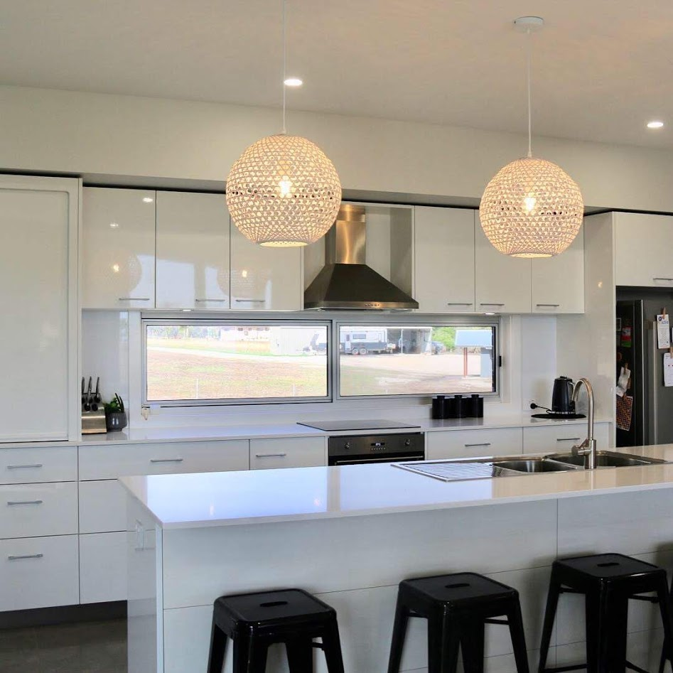 A white modern kitchen with smeg appliances.  A lovely feature with the glass window as a splashback.  Pendant cane light fittings work well in this Inverell Built home.