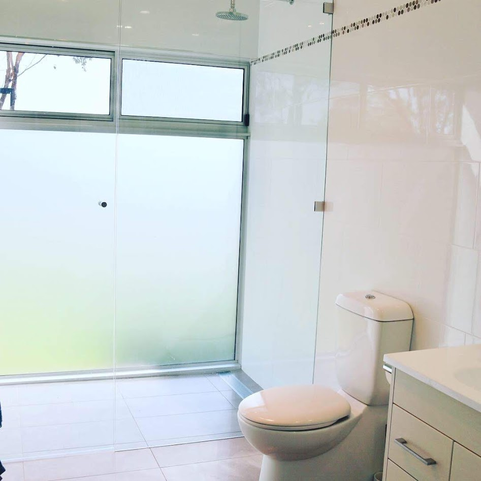 A compact bathroom with a full frosted glass wall to flood the area with light and warmth.  The frameless showerscreen is seemless.